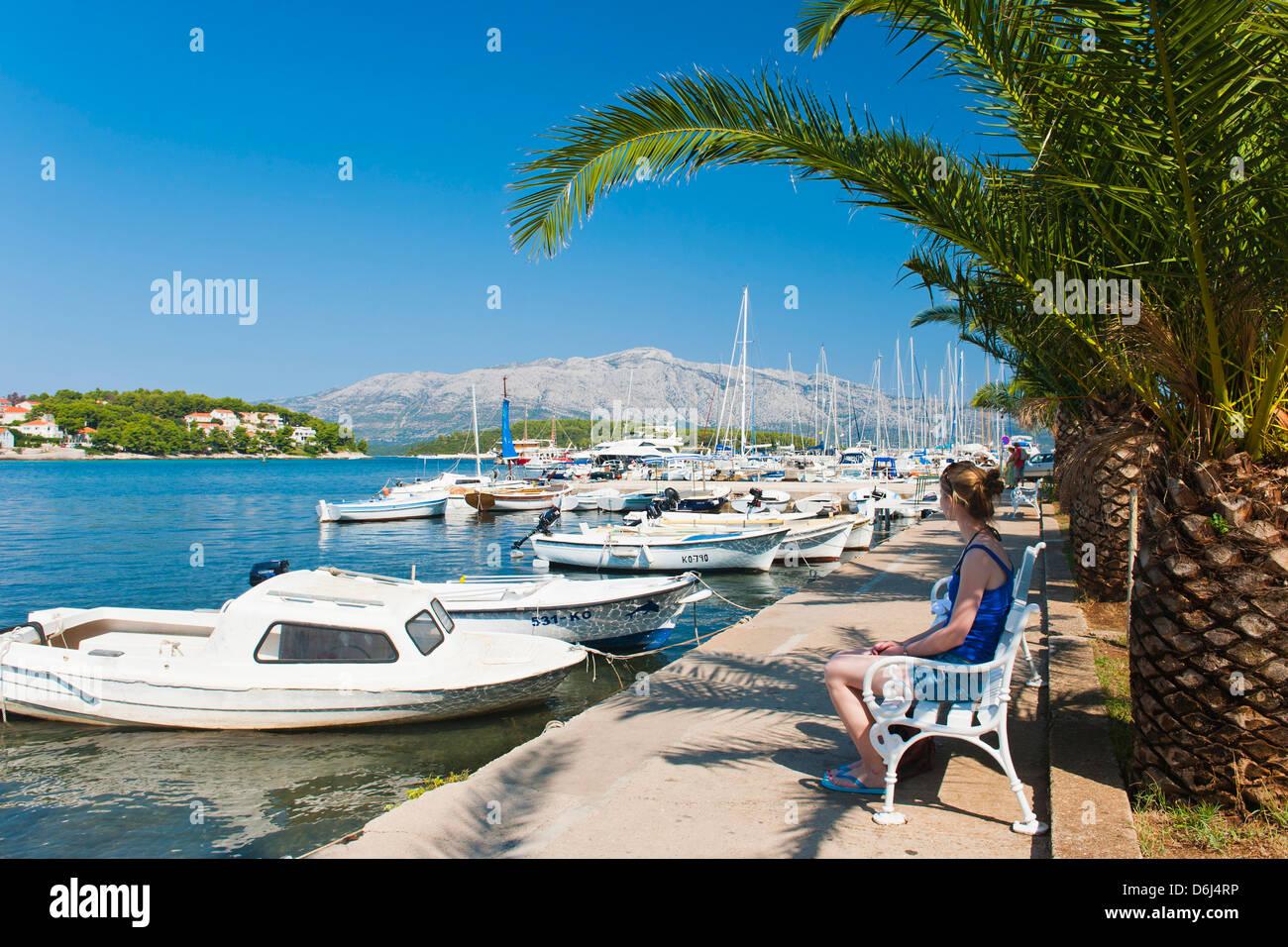 Tourist sitting in Lumbarda Harbor, Korcula Island, Dalmatian Coast, Adriatic, Croatia, Europe - Stock Image