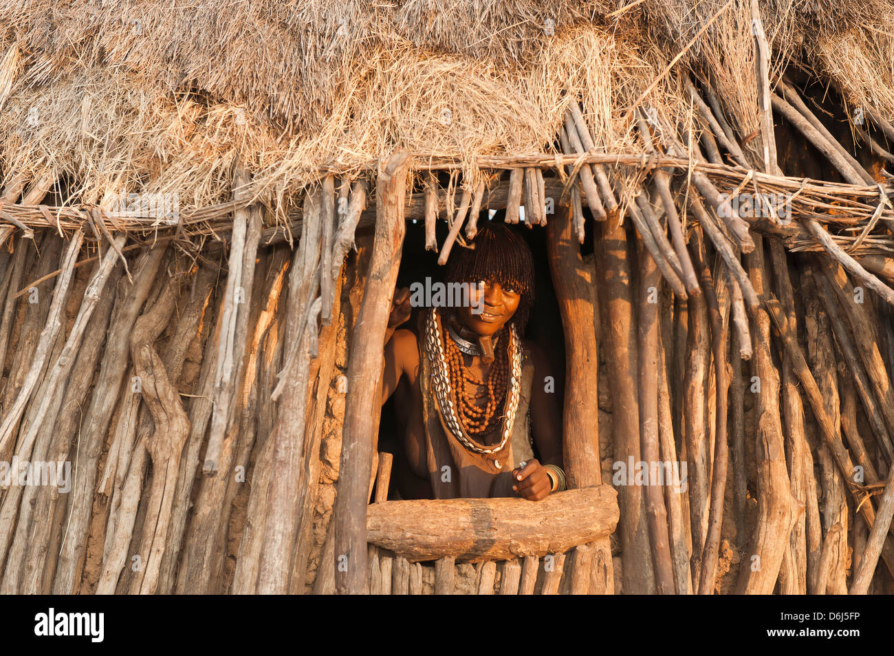 Pregnant Hamar woman with necklaces made of cowry shells coming out of her wooden hut, Omo River Valley, Southern - Stock Image