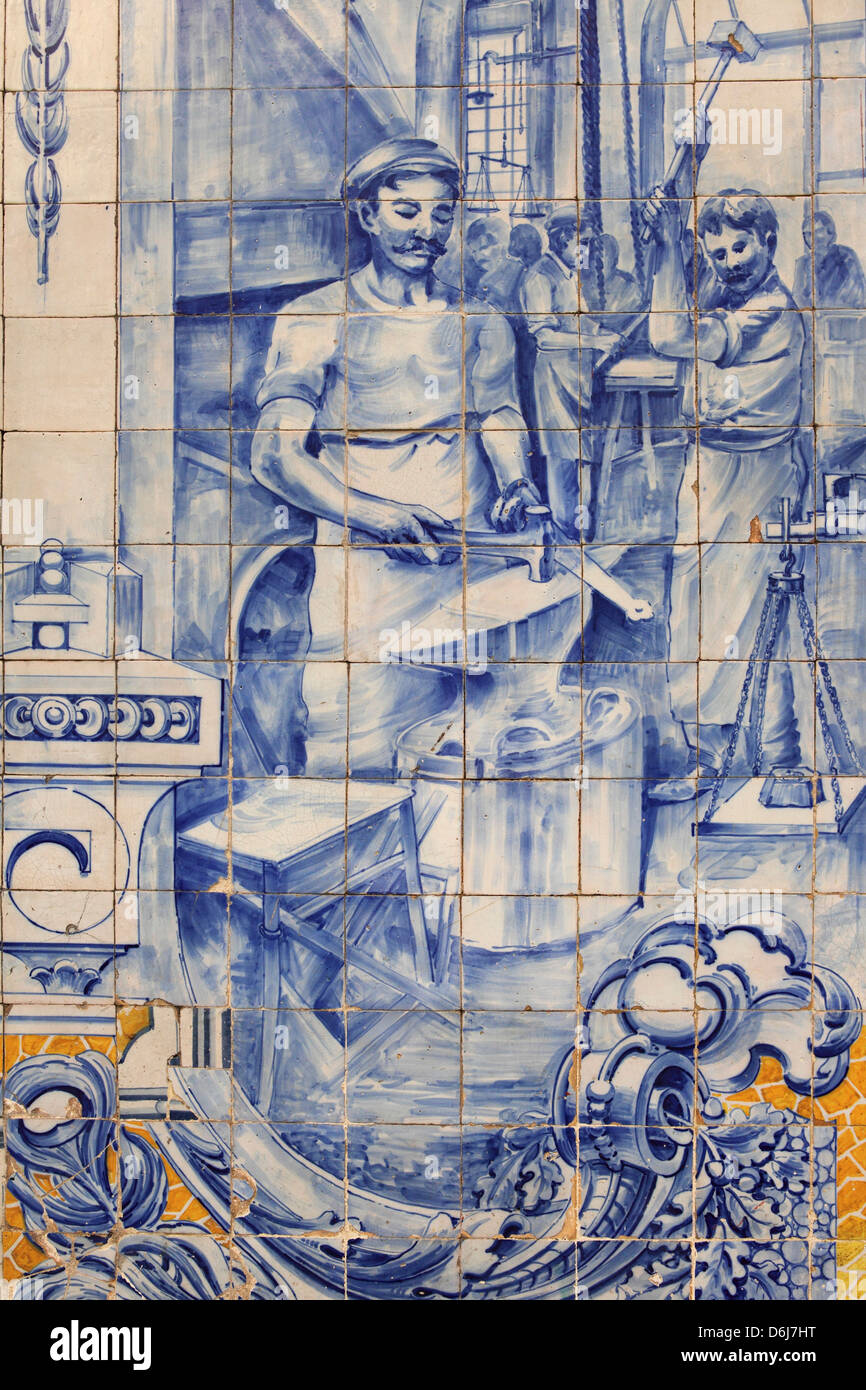 A blacksmith's workshop depicted on traditional Portuguese Azulejo tiles on a building in Alfama, Lisbon, Portugal, - Stock Image