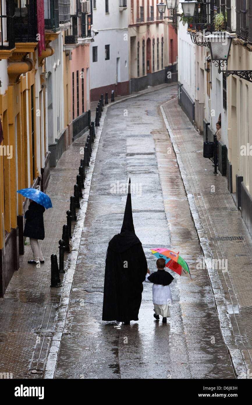 Penitents during Semana Santa (Holy Week) along rainy street, Seville, Andalucia, Spain, Europe - Stock Image