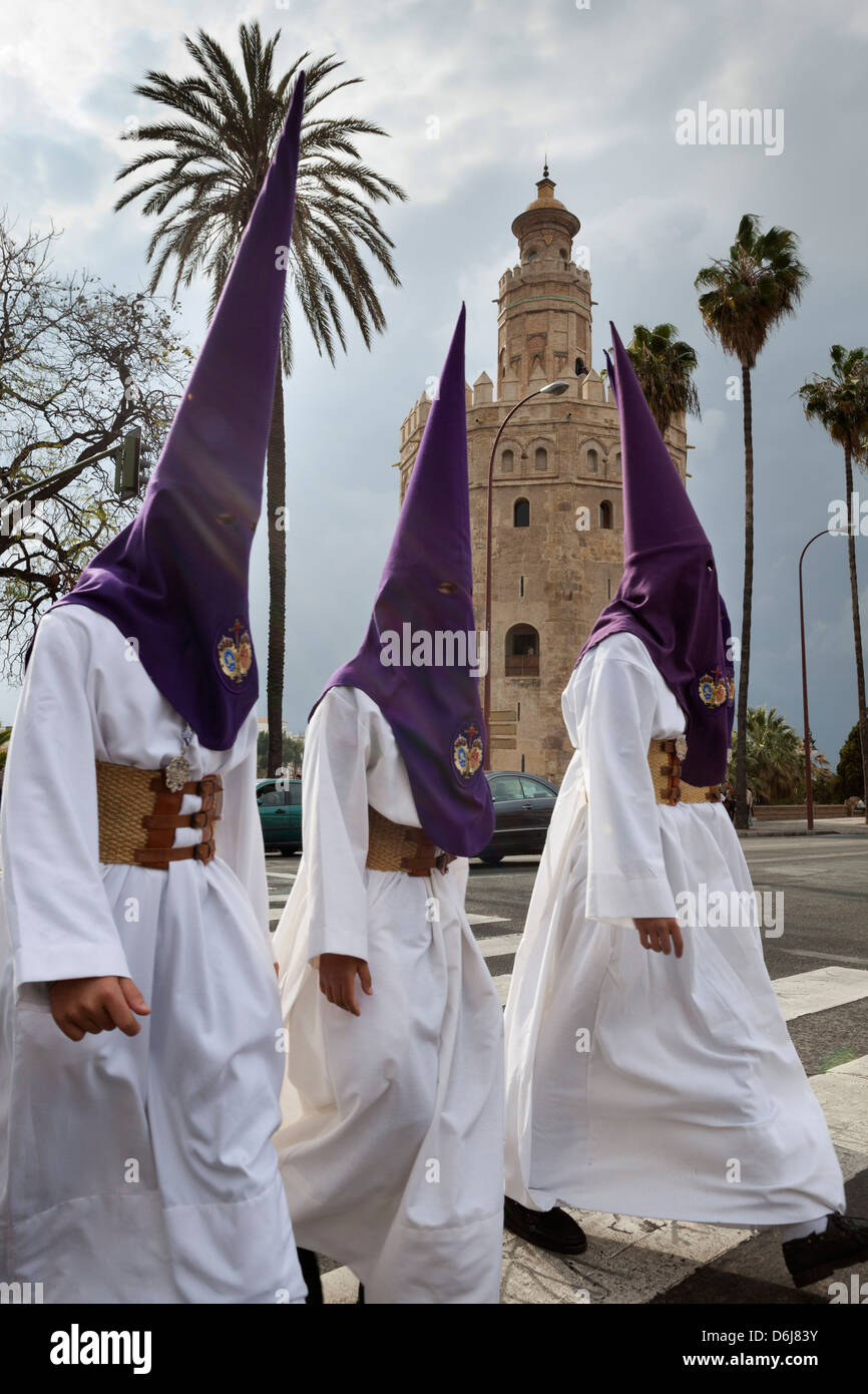 Penitents during Semana Santa (Holy Week) beneath Torre del Oro, Seville, Andalucia, Spain, Europe - Stock Image