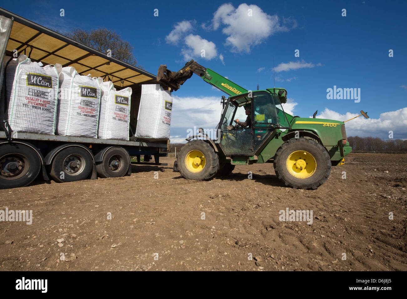 John Deere tele handler unloading bags of Scottish seed potatoes from a lorry - Stock Image