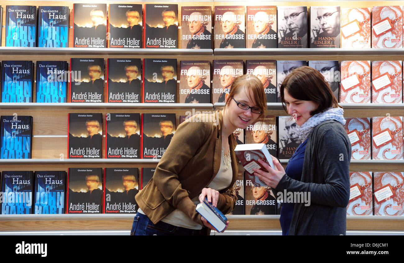 Two young women look at books at the stand of the Random House group at Leipzig Book Fair in Leipzig,Germany, - Stock Image