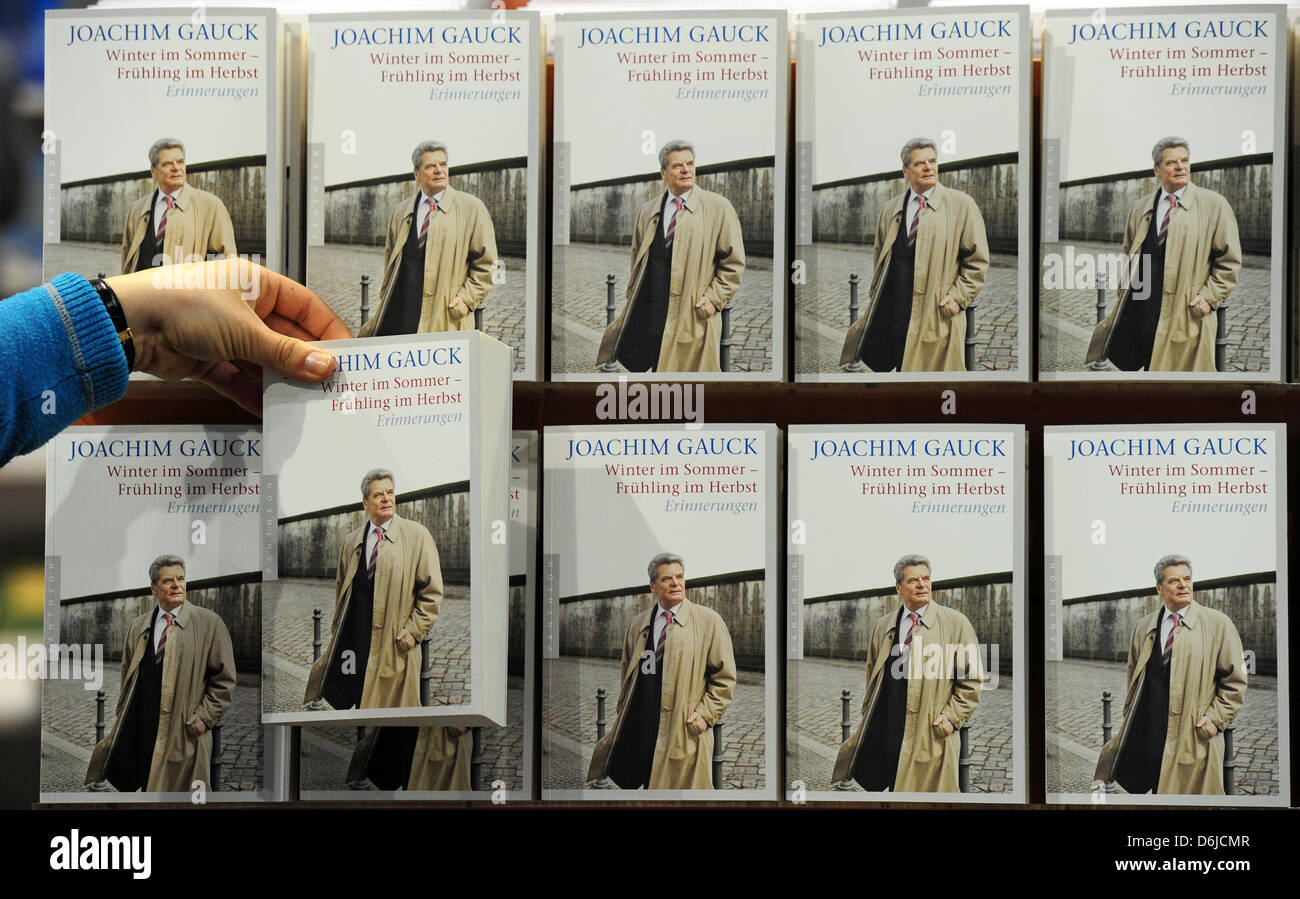 A woman puts copies of the Memoirs of Joachim Gauck on a shelf at the Leipzig Book Fair bookstore in Leipzig,Germany, - Stock Image
