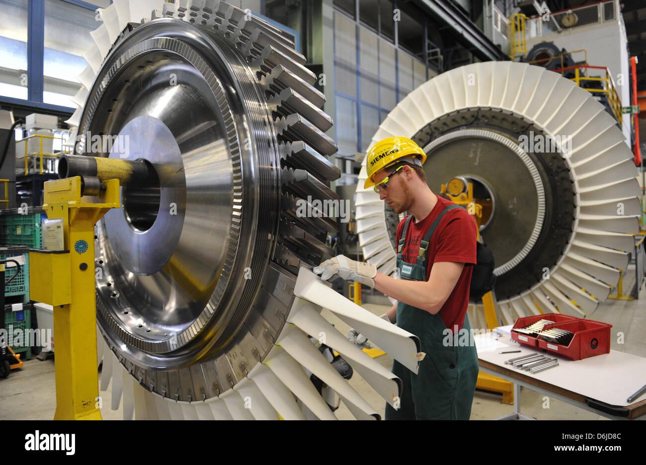 A Siemens employee works on a turbine blade wheel on the