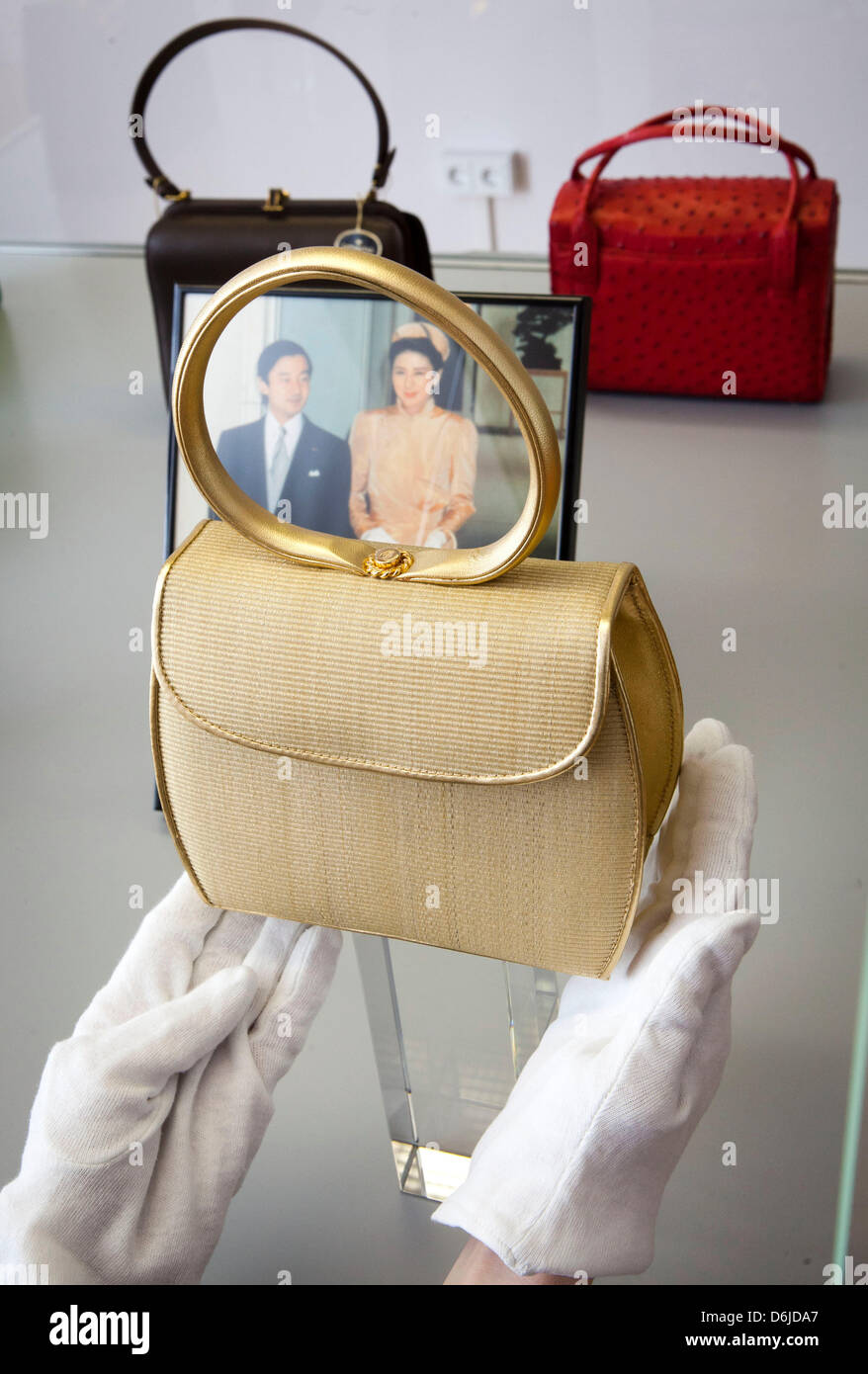 A restaurator places a handbag in front of a picture of the marriage of Japanese Crown Prince Naruhito with Crown - Stock Image