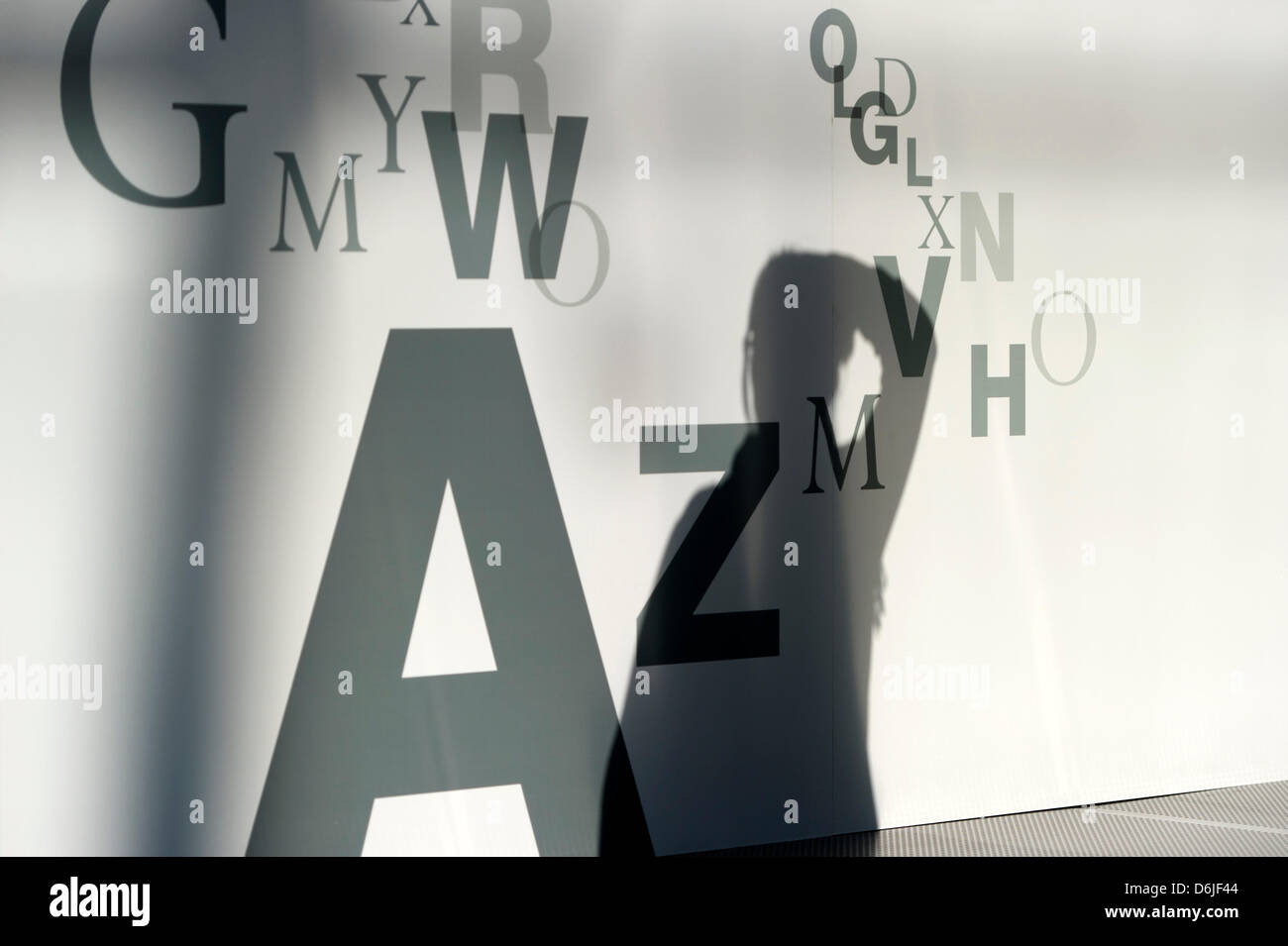 The silhouette of a visitor of the Leipzig Book Fair is visible on a wall covered with letters in Leipzig, Germany, - Stock Image