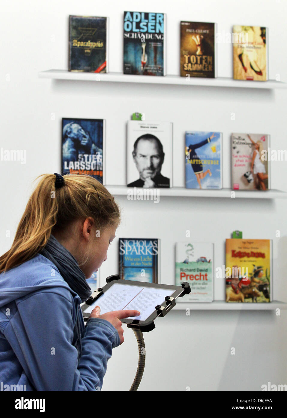 A visitor reads an eBook at the stand of PagePlace at the Leipzig Book Fair in Leipzig, Germany, 16 March 2012. - Stock Image
