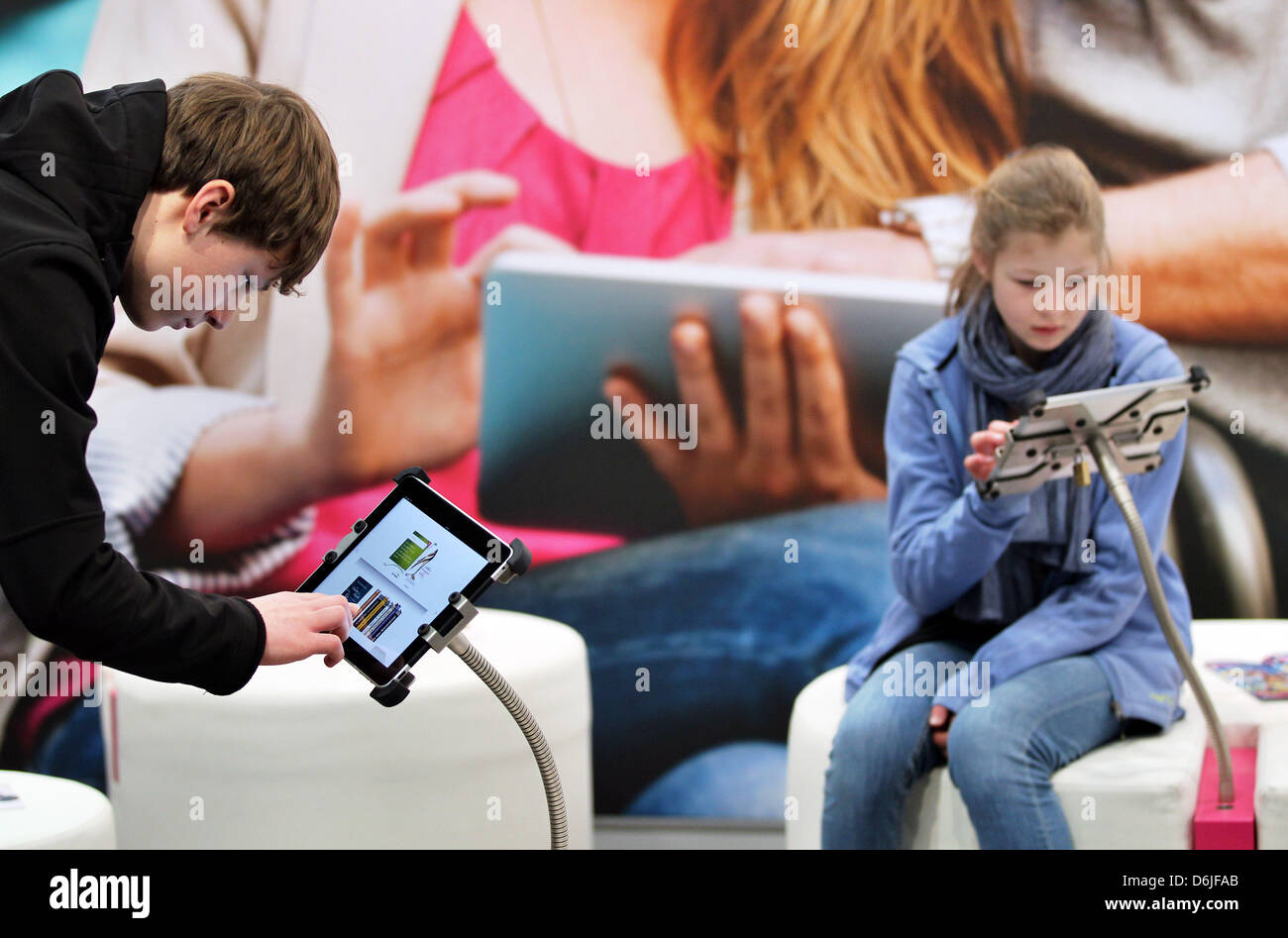 Visitors read an eBook at the stand of PagePlace at the Leipzig Book Fair in Leipzig, Germany, 16 March 2012. PagePlace - Stock Image