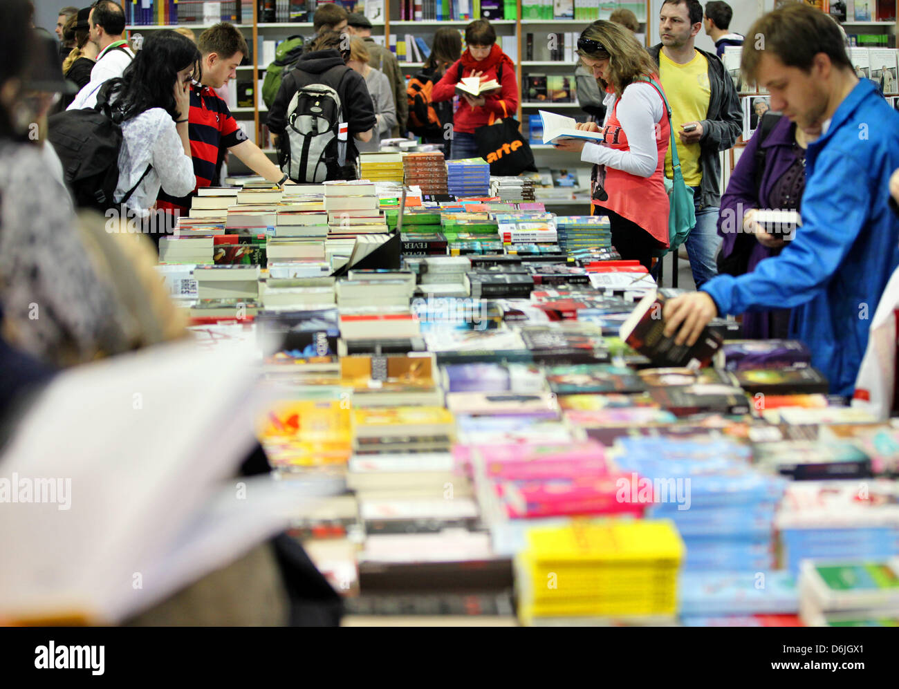 Visitors look through books ona table at the Leipzig Book Fair in Leipzig, Germany, 18 March 2012. 2071 publishers - Stock Image