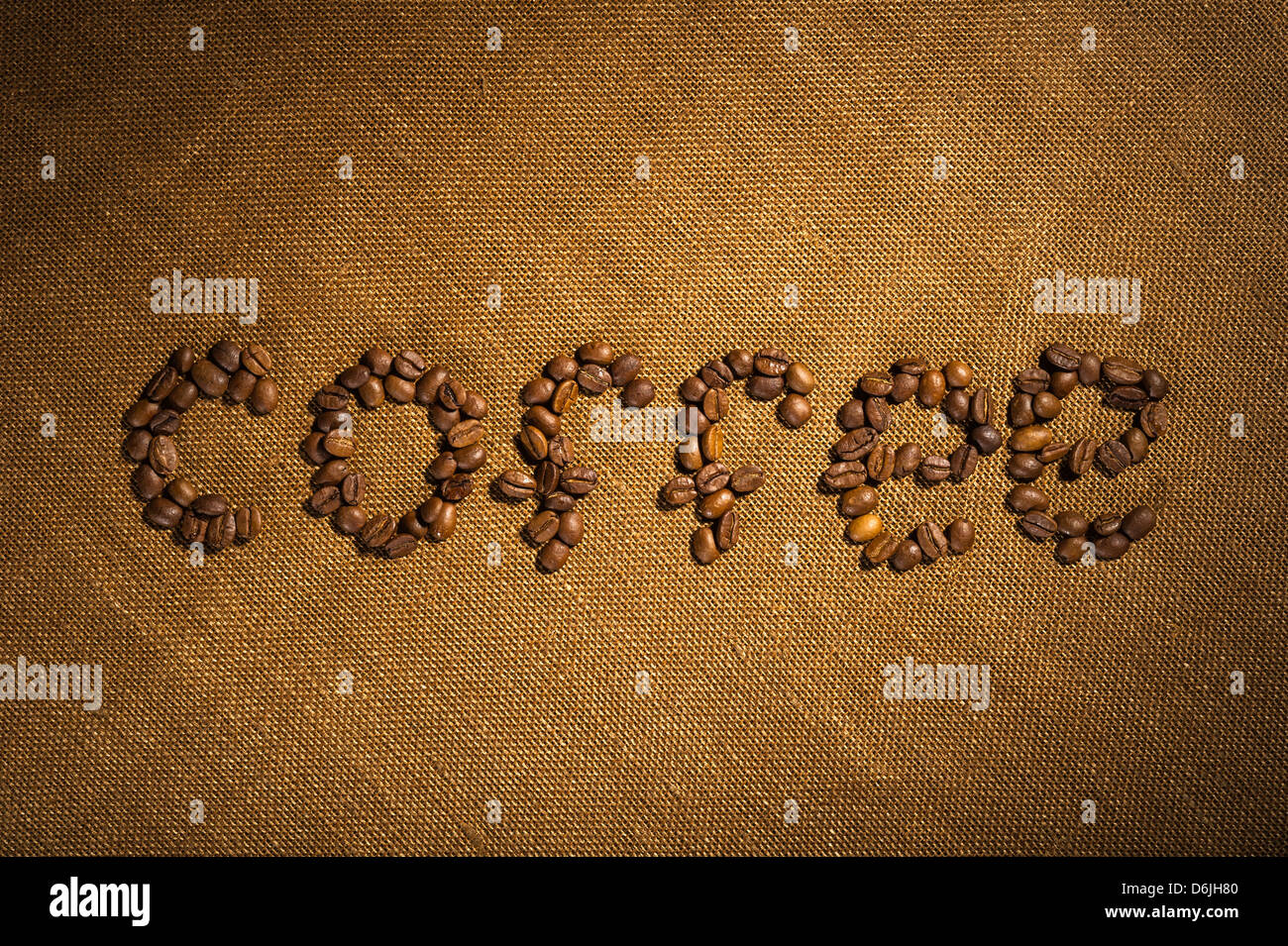 The word coffee made from coffee beans on fabric texture Stock Photo