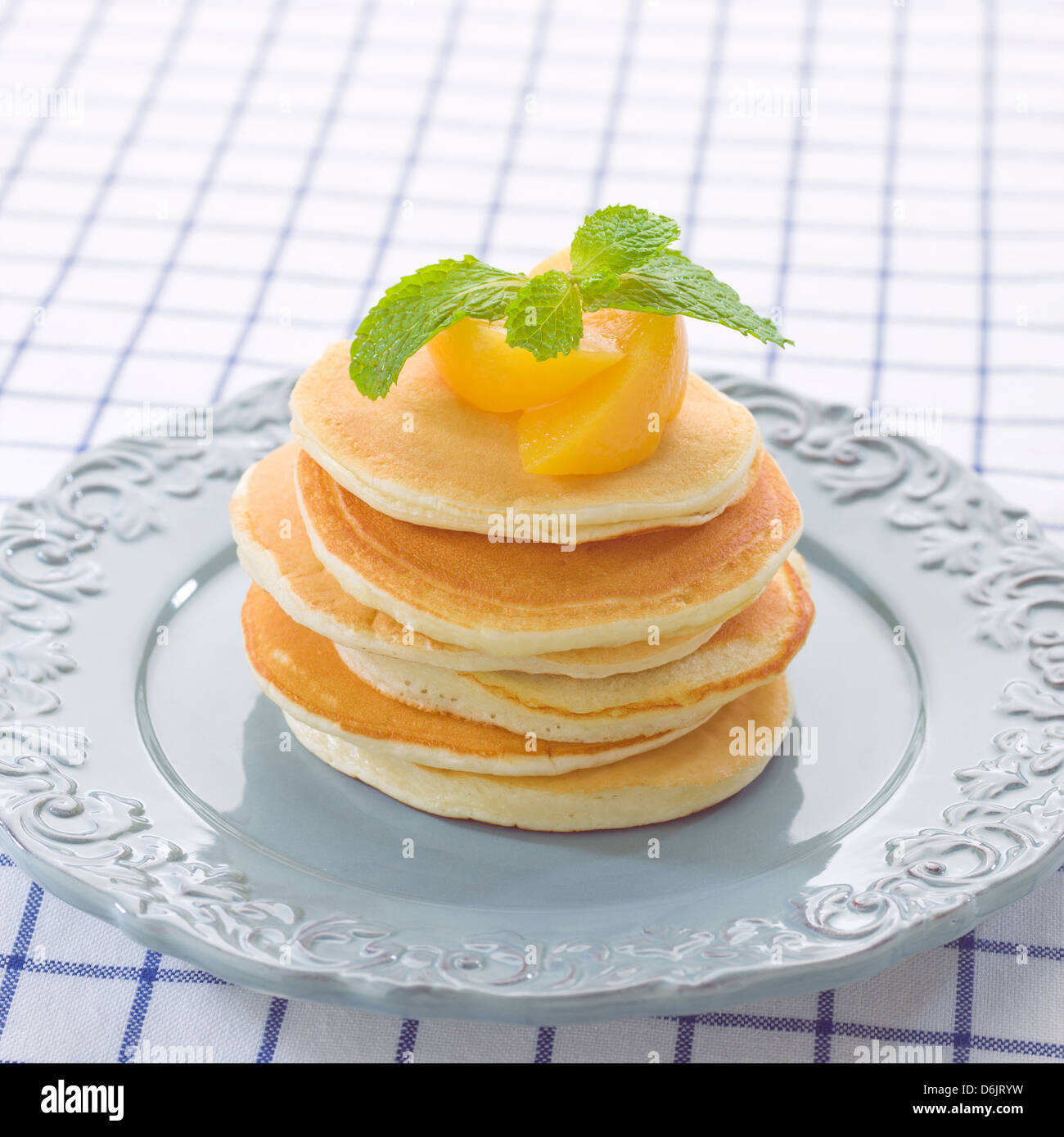Golden pancakes topping with peach and mint - Stock Image