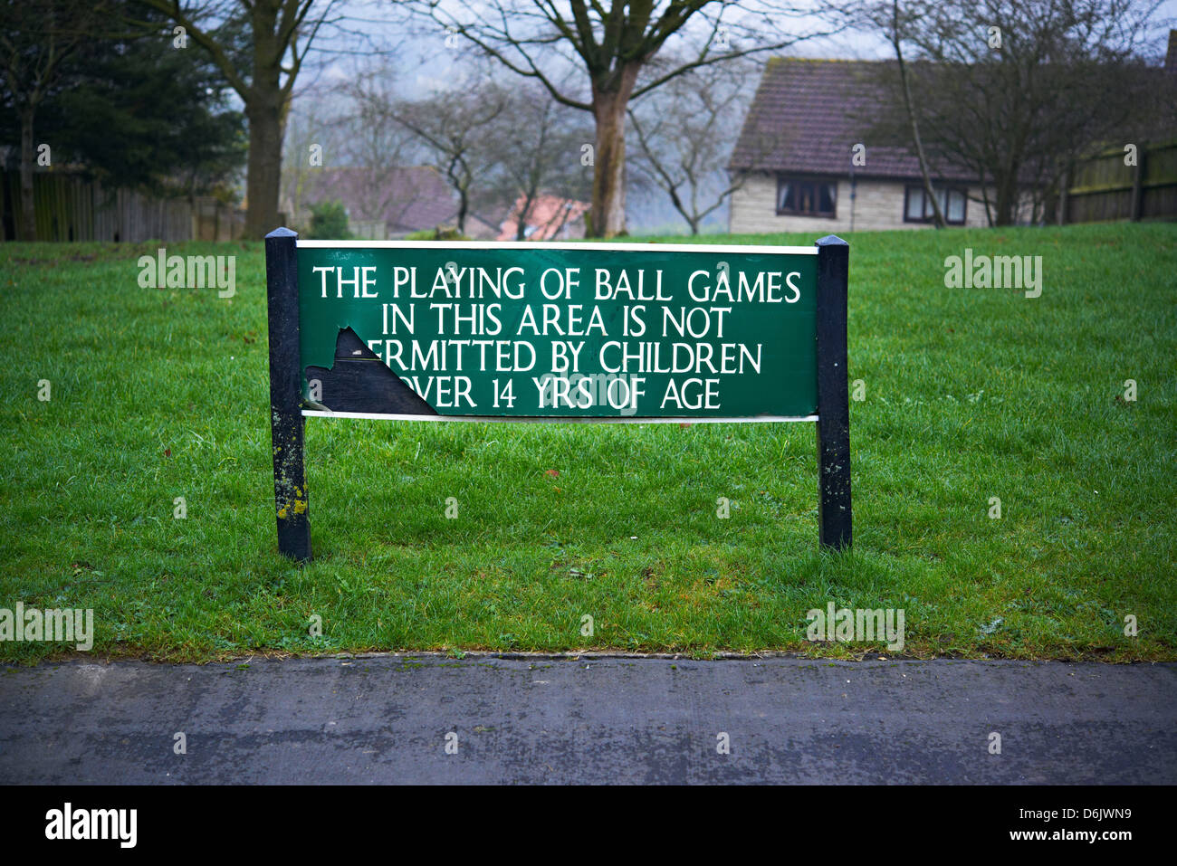 A sign saying the playing of ball games in this area is not permitted by children over 14 years of age - Stock Image