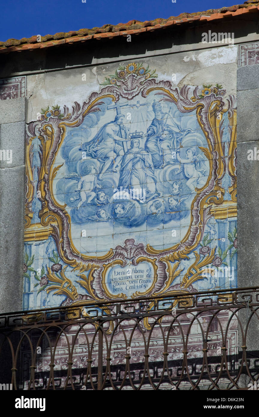 Blue and white tiled azuleju tableau with elaborate gold tiled frame preserved in an old wall in the City of Oporto, - Stock Image