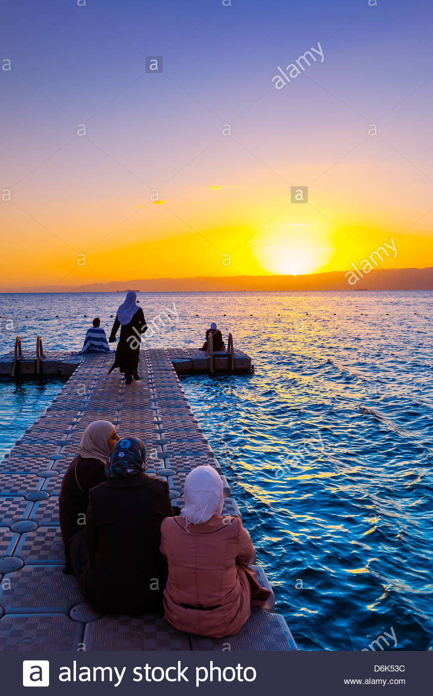 Jordanian women watching the sunset across the Gulf of Aqaba, Red Sea, Jordan from a dock at the Radisson Blu Tala - Stock Image