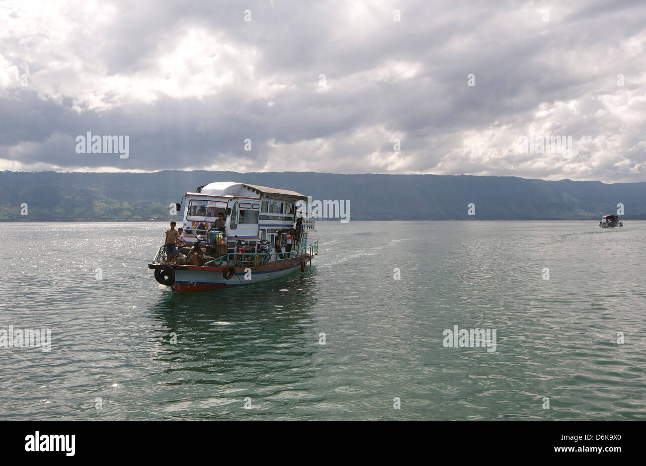Ferry boat on Lake Toba arriving into Parapat beneath gathering monsoon clouds, Sumatra, Indonesia, Southeast Asia, - Stock Image