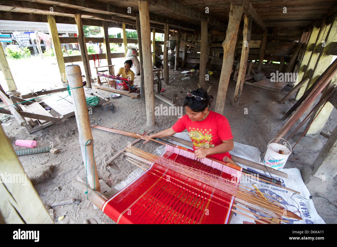 Batak woman weaving Batak Toba sarong beneath her Batak house, Buhit, Samosir Island, Lake Toba, Sumatra, Indonesia Stock Photo