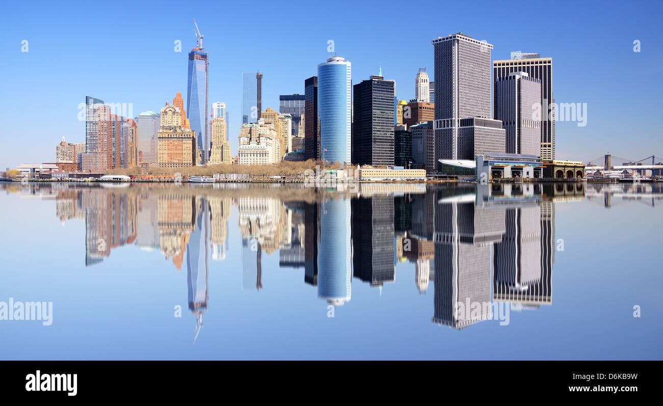Lower Manhattan financial district skyline in New York City with reflections. - Stock Image