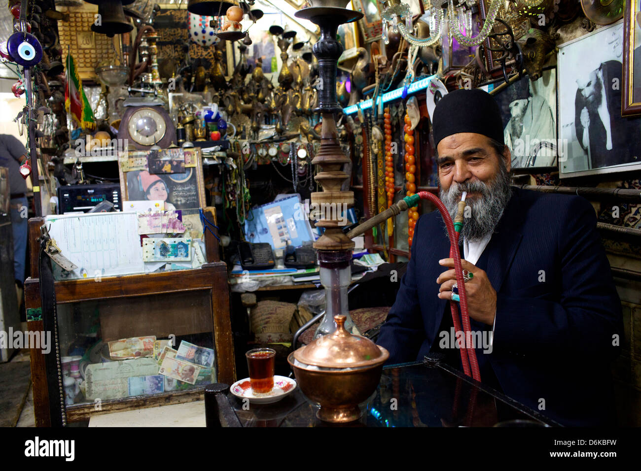 An old man smoking narguile in the bazaar of Isfahan, Iran, Middle East - Stock Image