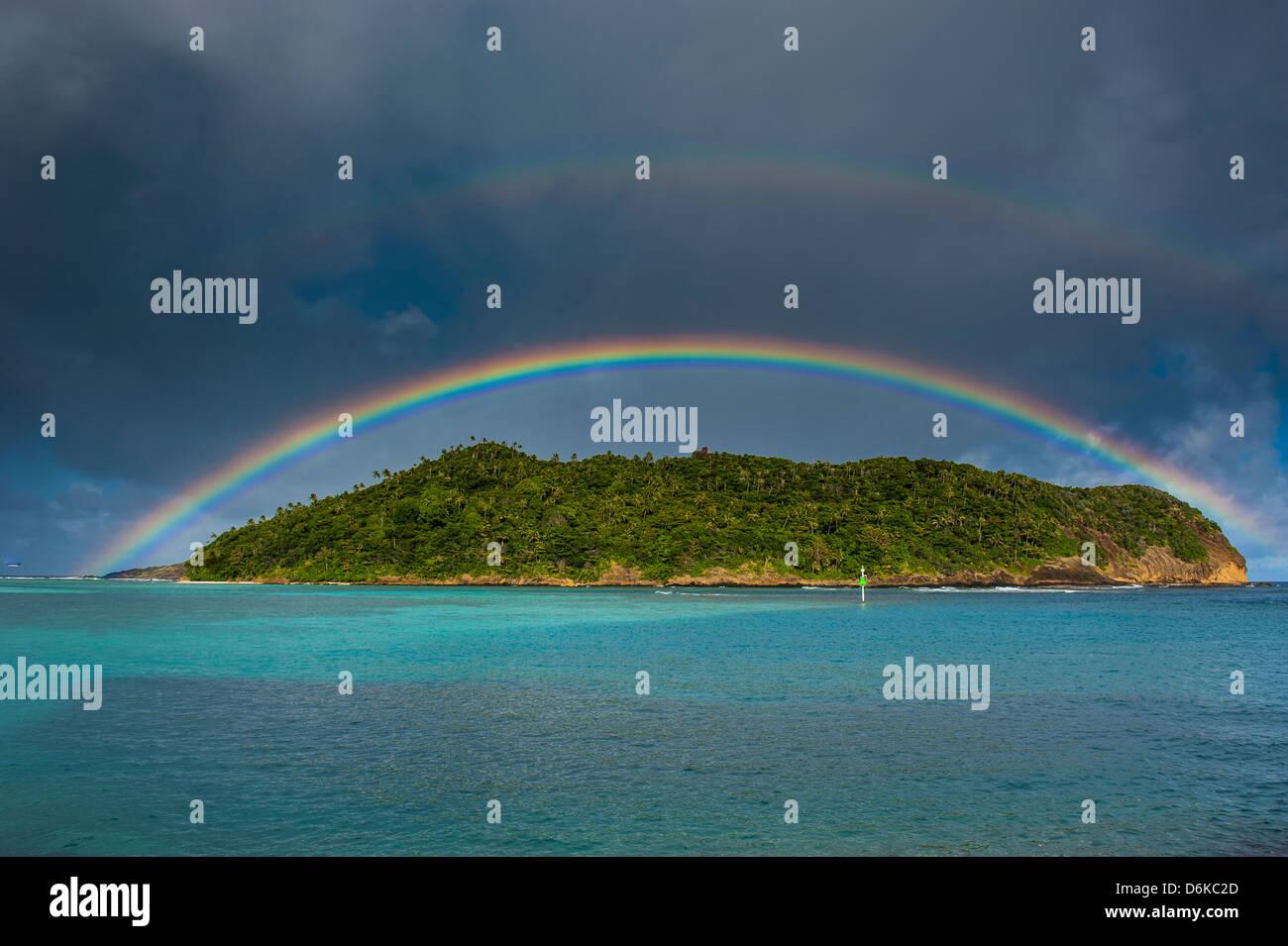 Incredible rainbow over an islet off Ofu Island, Manua Island group, American Samoa, South Pacific, Pacific - Stock Image