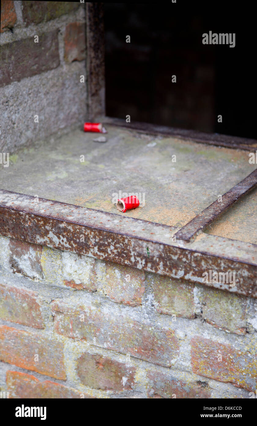 Spent cartridge in window of deserted house in the village of Imber, Salisbury Plain, Wiltshire - Stock Image