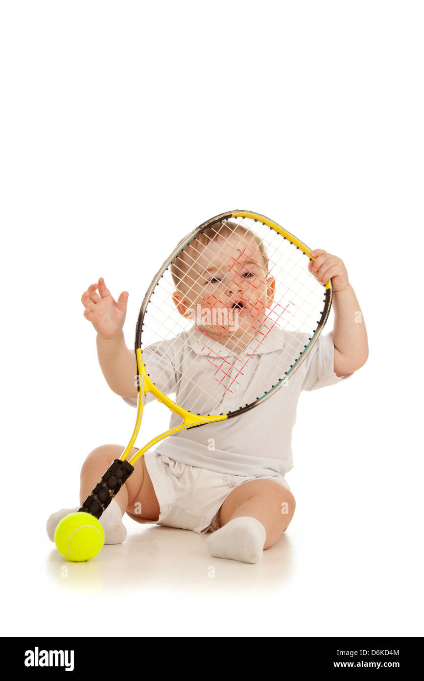 adorable child floor and playing with tennis racket and ball over white background - Stock Image