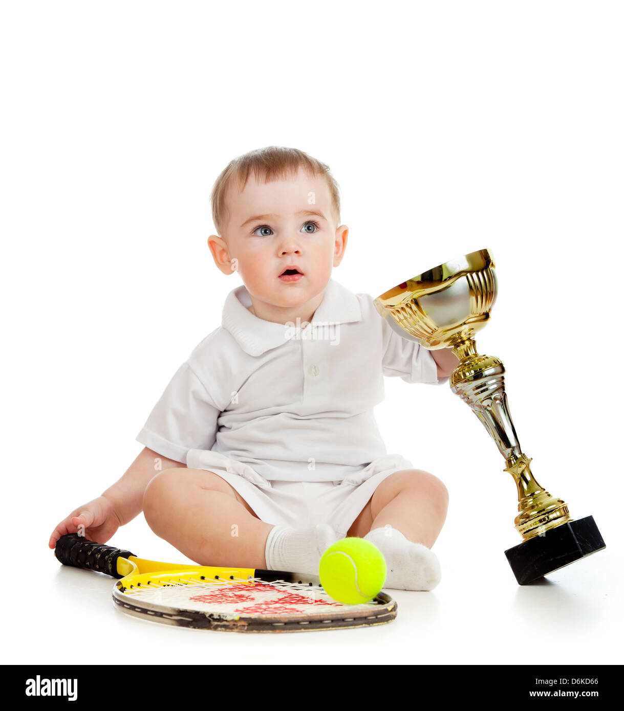 adorable child playing with tennis racket and cup over white background - Stock Image