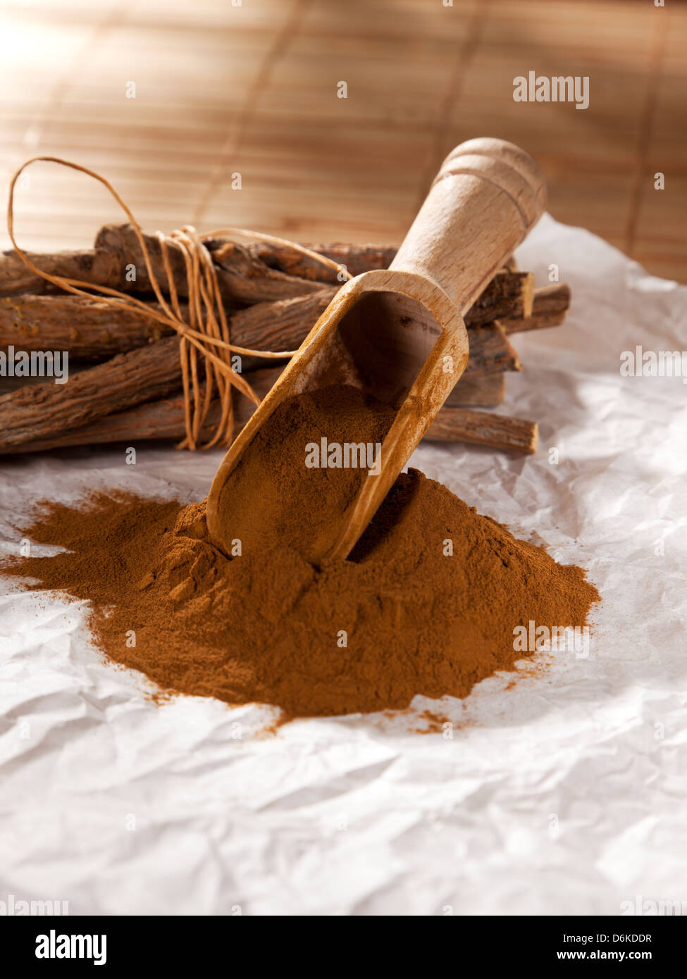 Heap of ground licorice and bundled liquorice roots - Stock Image