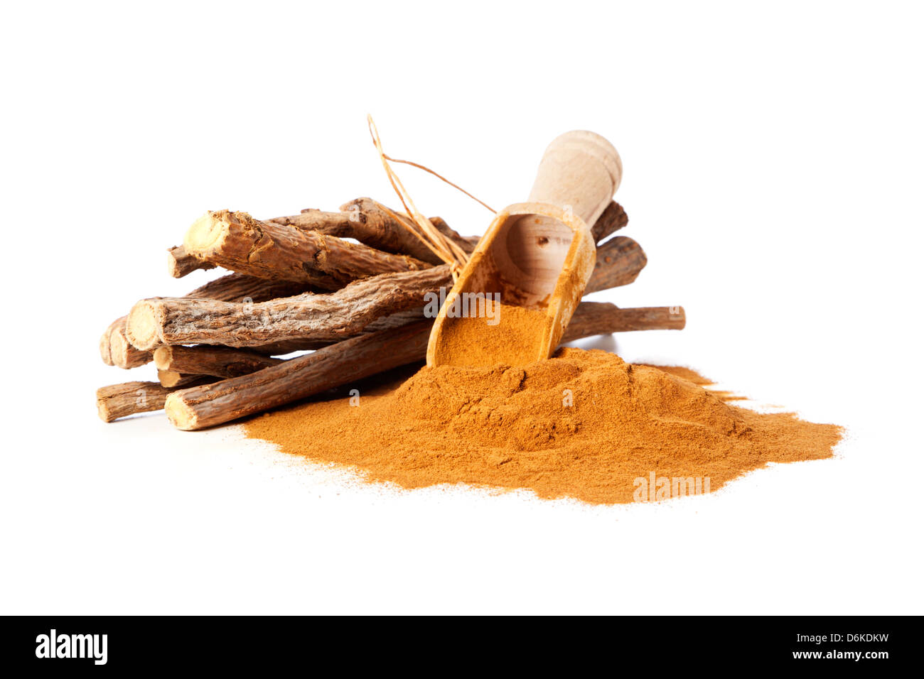 Heap of ground liquorice with wooden shovel and bundle of native liquorice roots - Stock Image