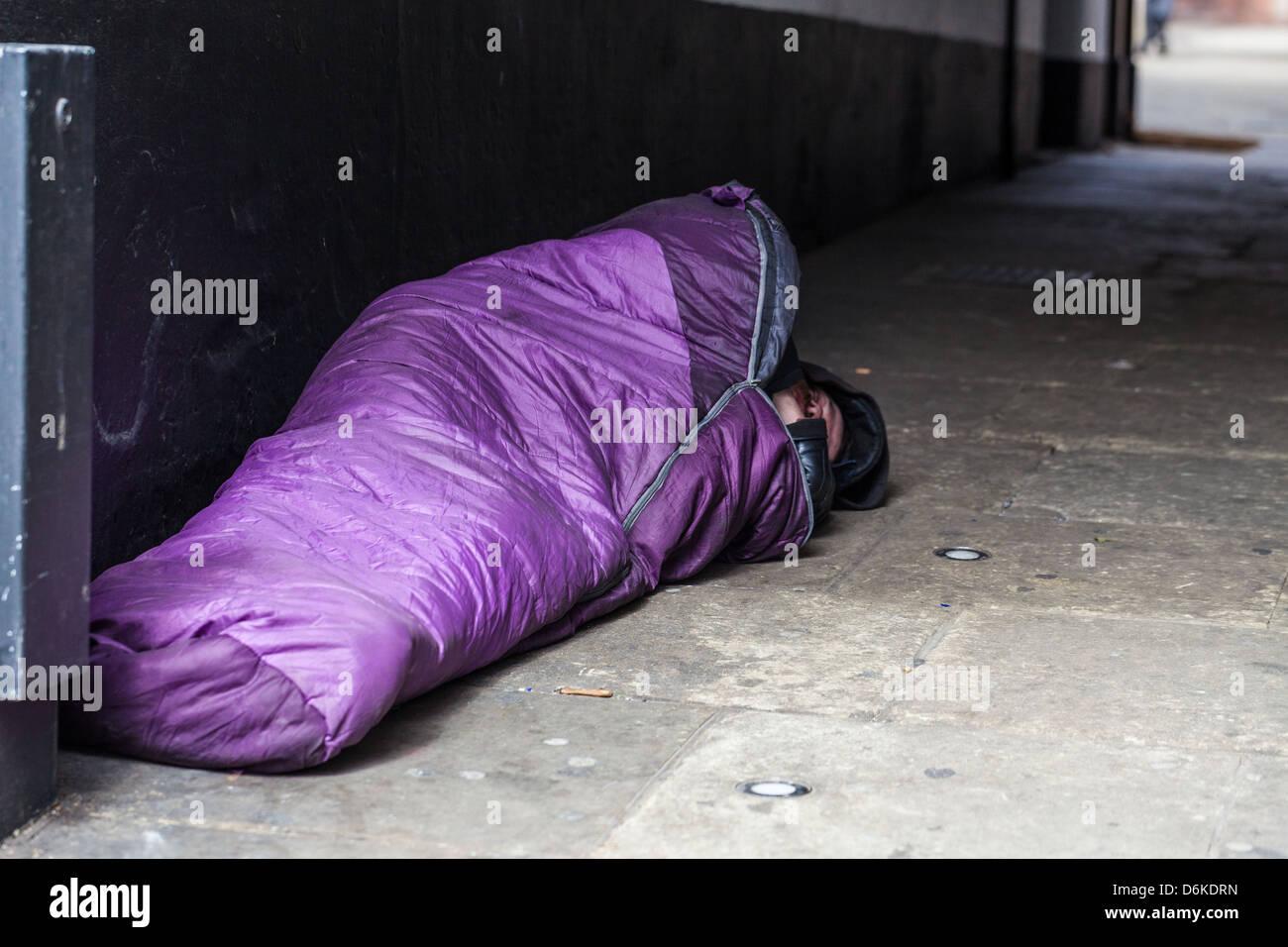 Homeless man sleeping rough in a sleeping bag, London, England, UK. - Stock Image