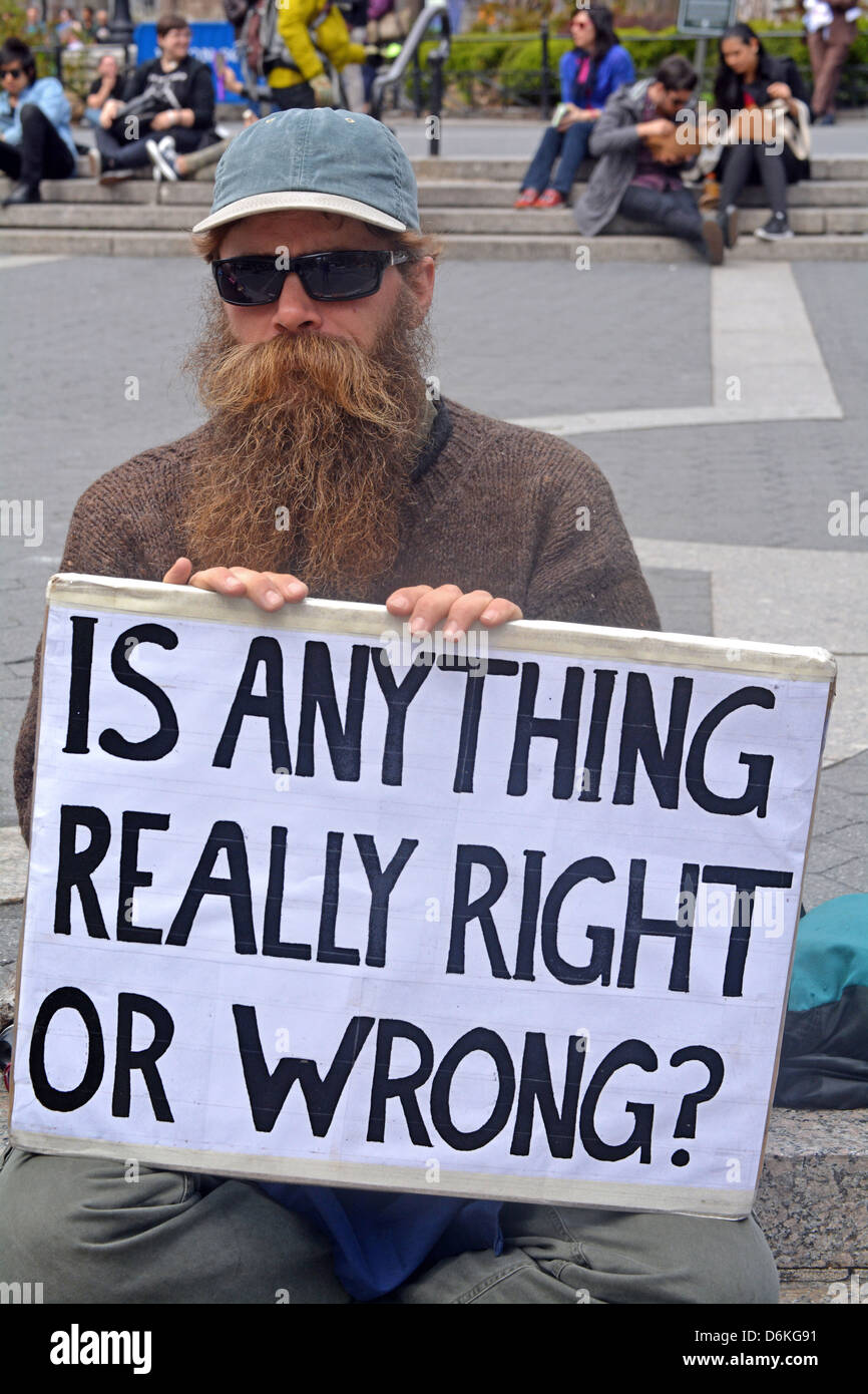 Man with a sign in Union Square Park asking 'Is anything really right or wrong?' - Stock Image
