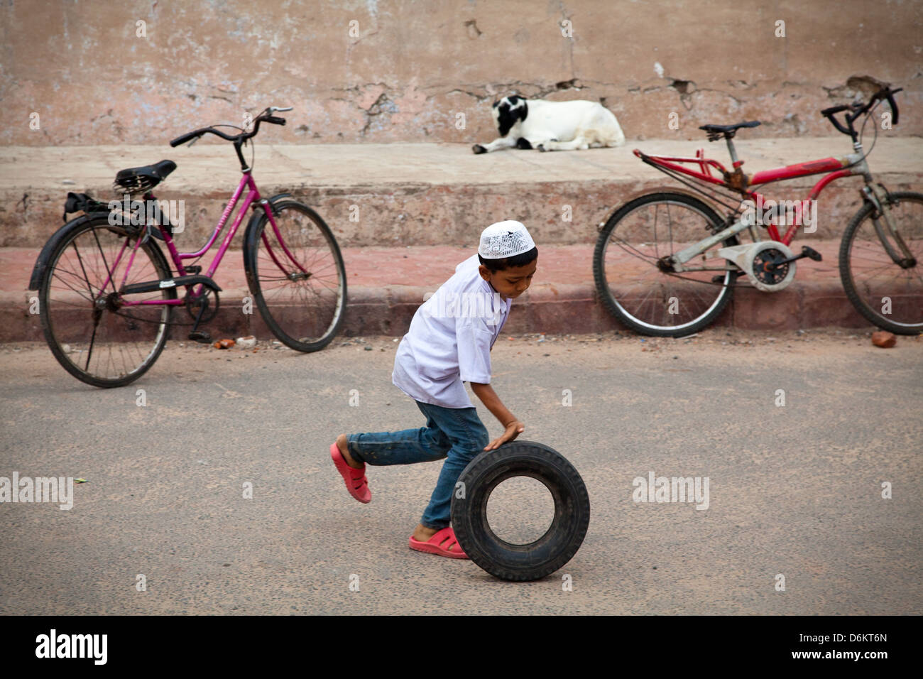 An Indian boy plays with a tyre, Ahmedabad, India - Stock Image