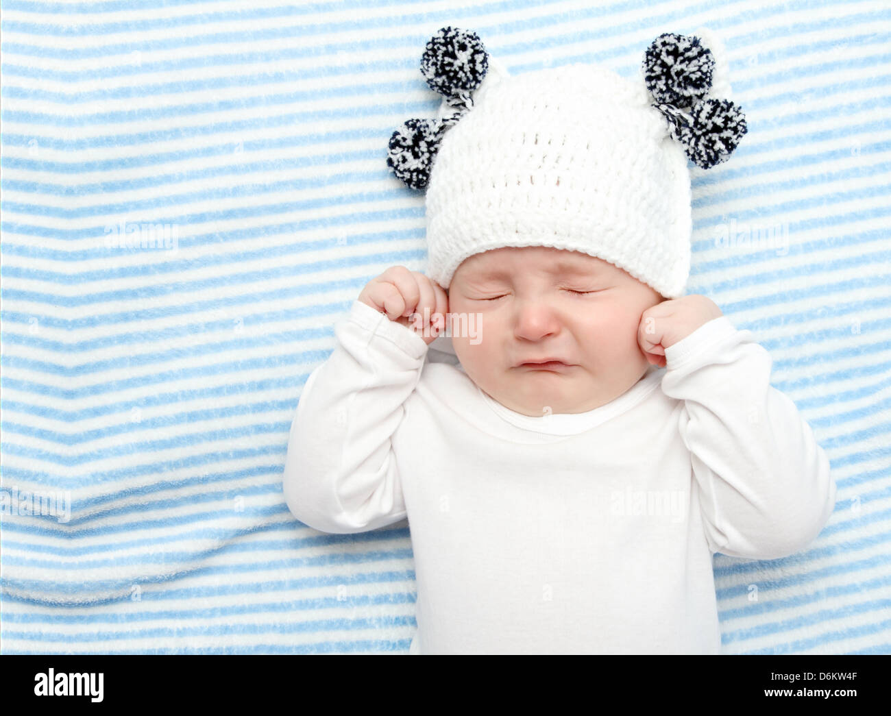little baby crying on bed - Stock Image