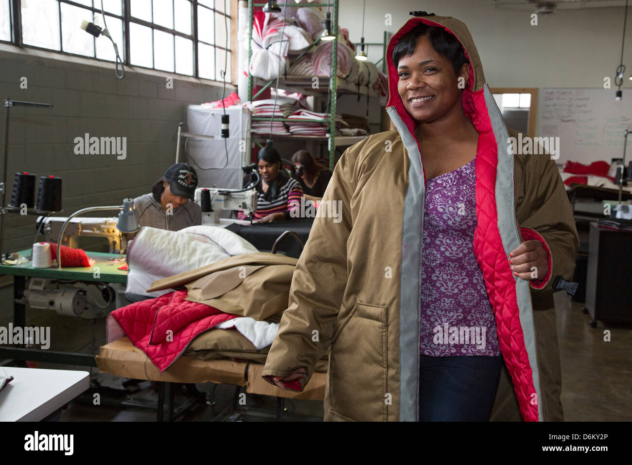 A worker at the nonprofit Empowerment Plan models a coat which formerly homeless women are making for homeless people. - Stock Image