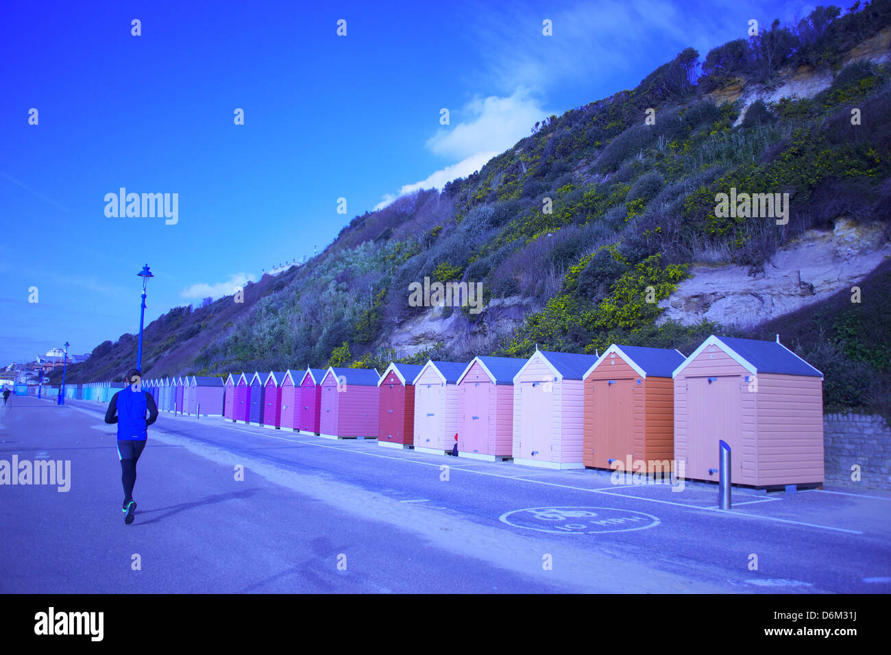 British seaside and the Beach Cabin in Bournemouth - A jogger promenades the colour and artistry that leads into - Stock Image