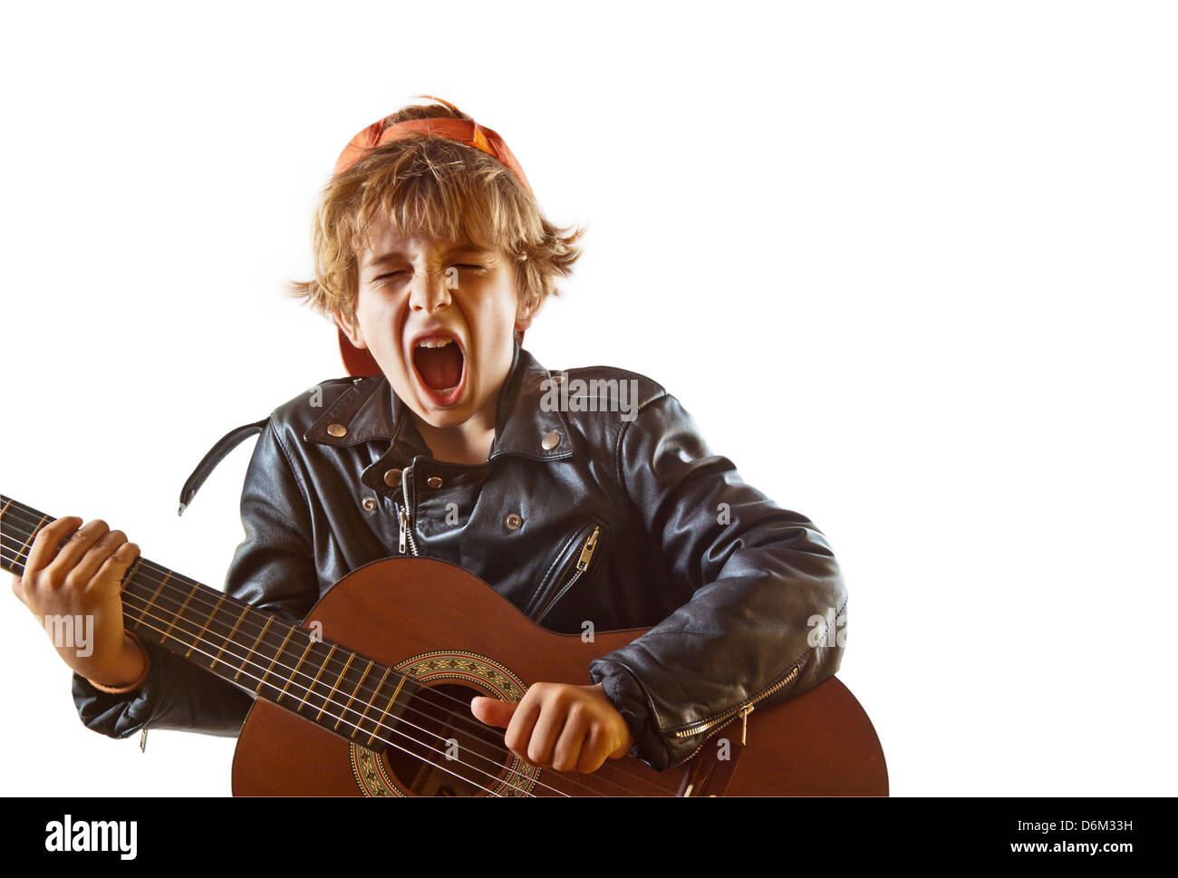 Cute small kid playing guitar with great concentration and attitude. White background, plenty of copy space. - Stock Image