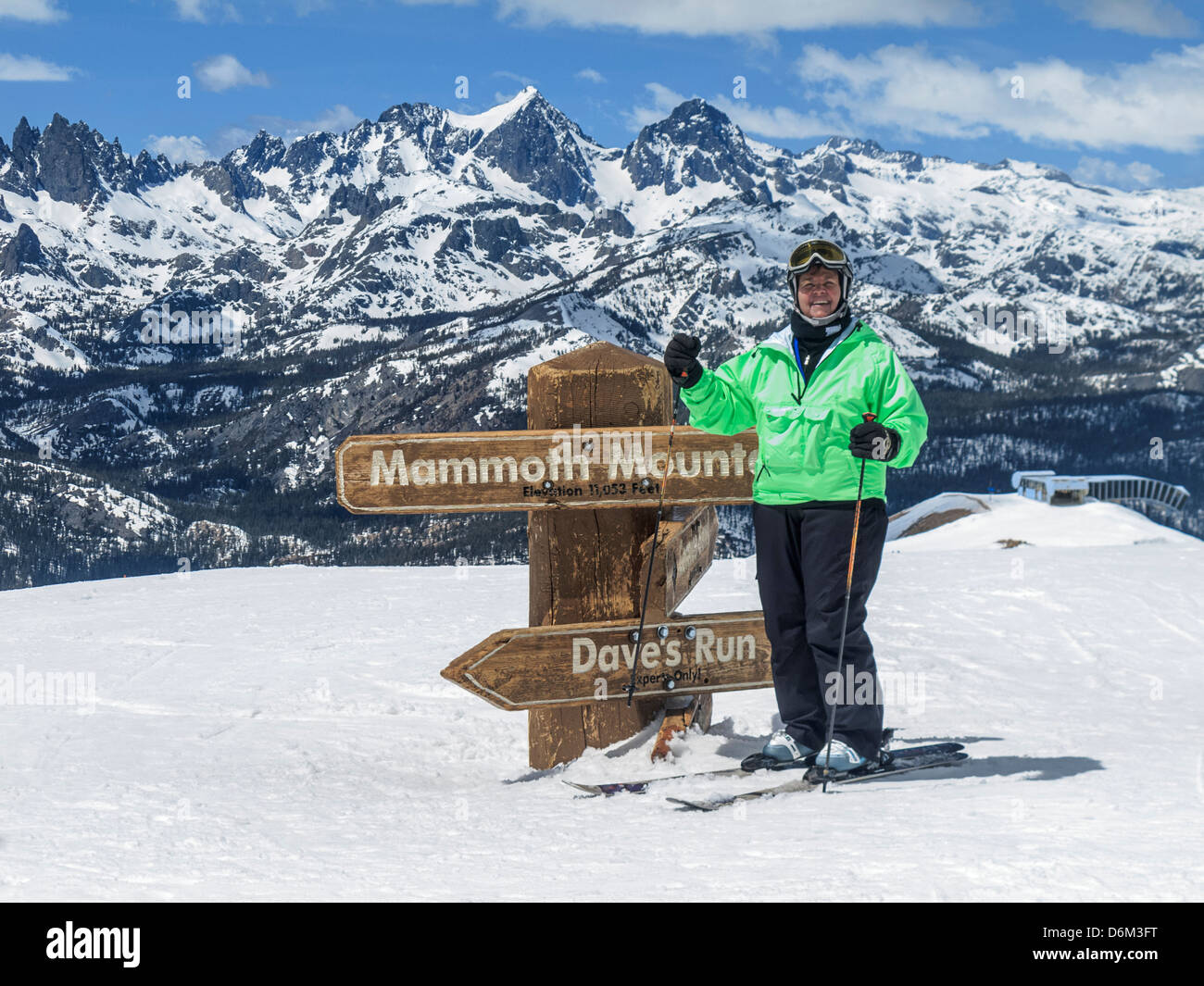 Woman wearing fancy ski wear at the top of Mammoth Mountain's expert runs, ready to put the technical skiwear - Stock Image