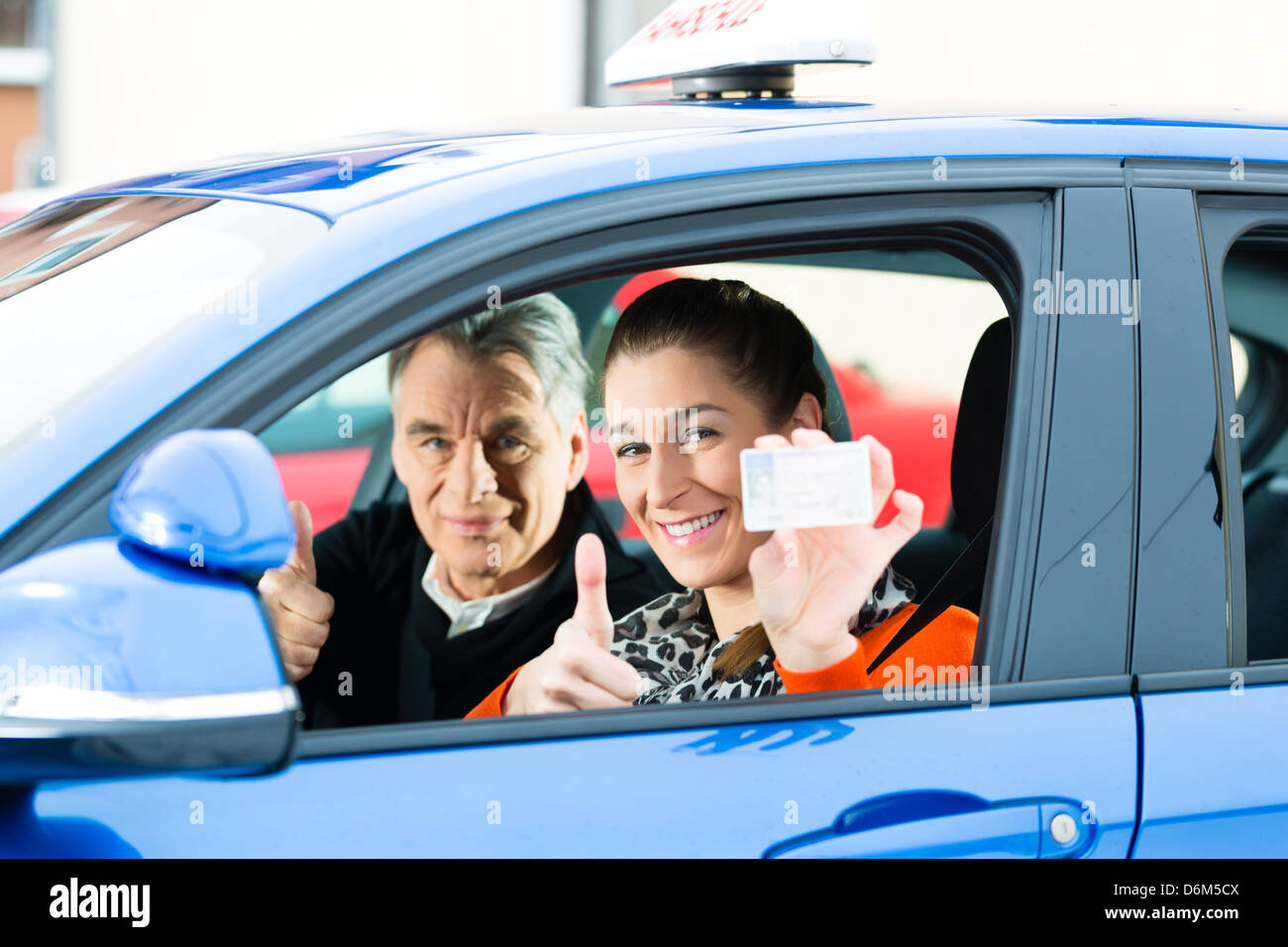 Driving School - Young woman steer a car, maybe she has a driving test, she holding proudly her driving license - Stock Image