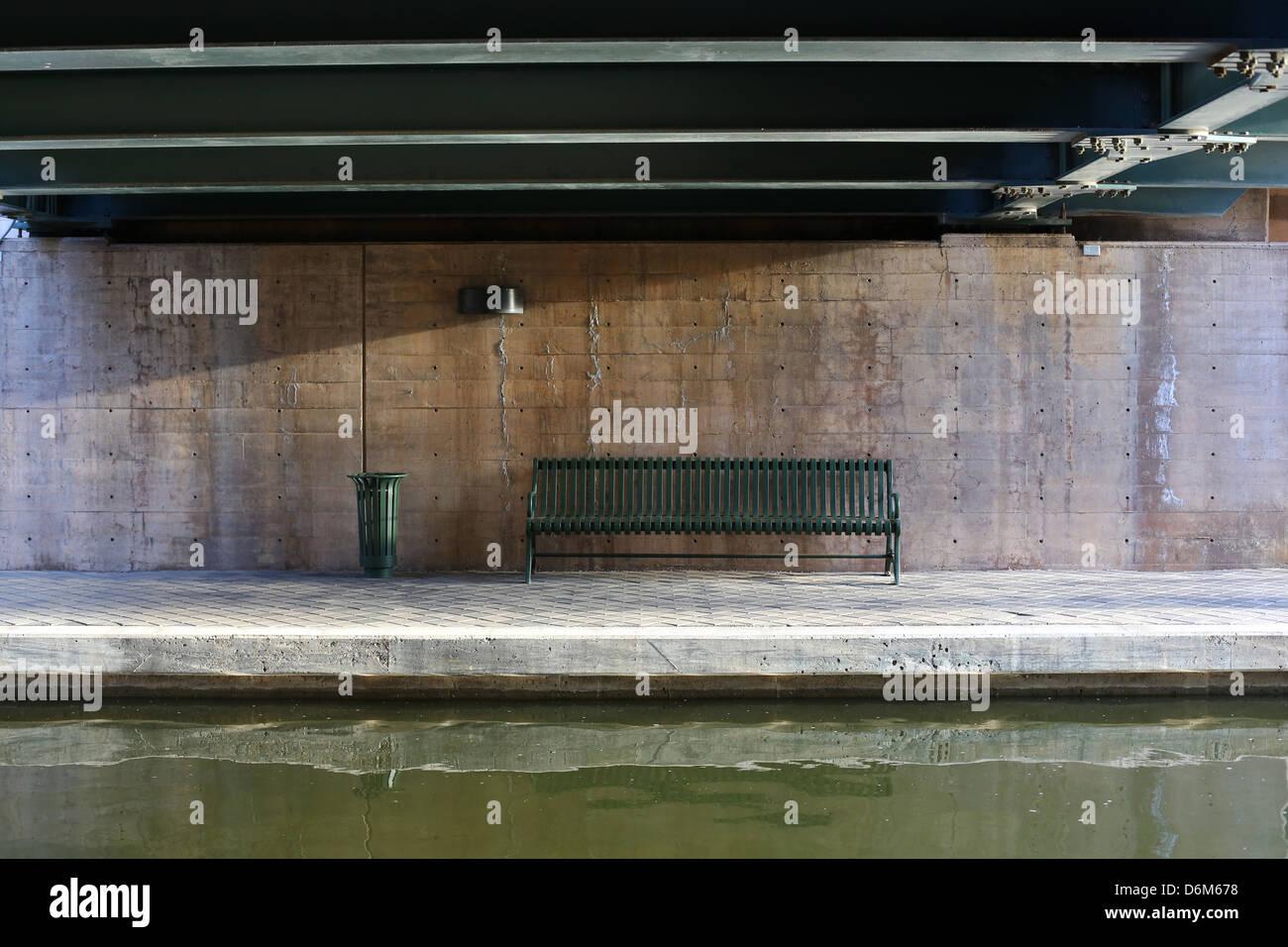 An empty park bench under a bridge, next to a river in Oklahoma City, Oklahoma. Stock Photo