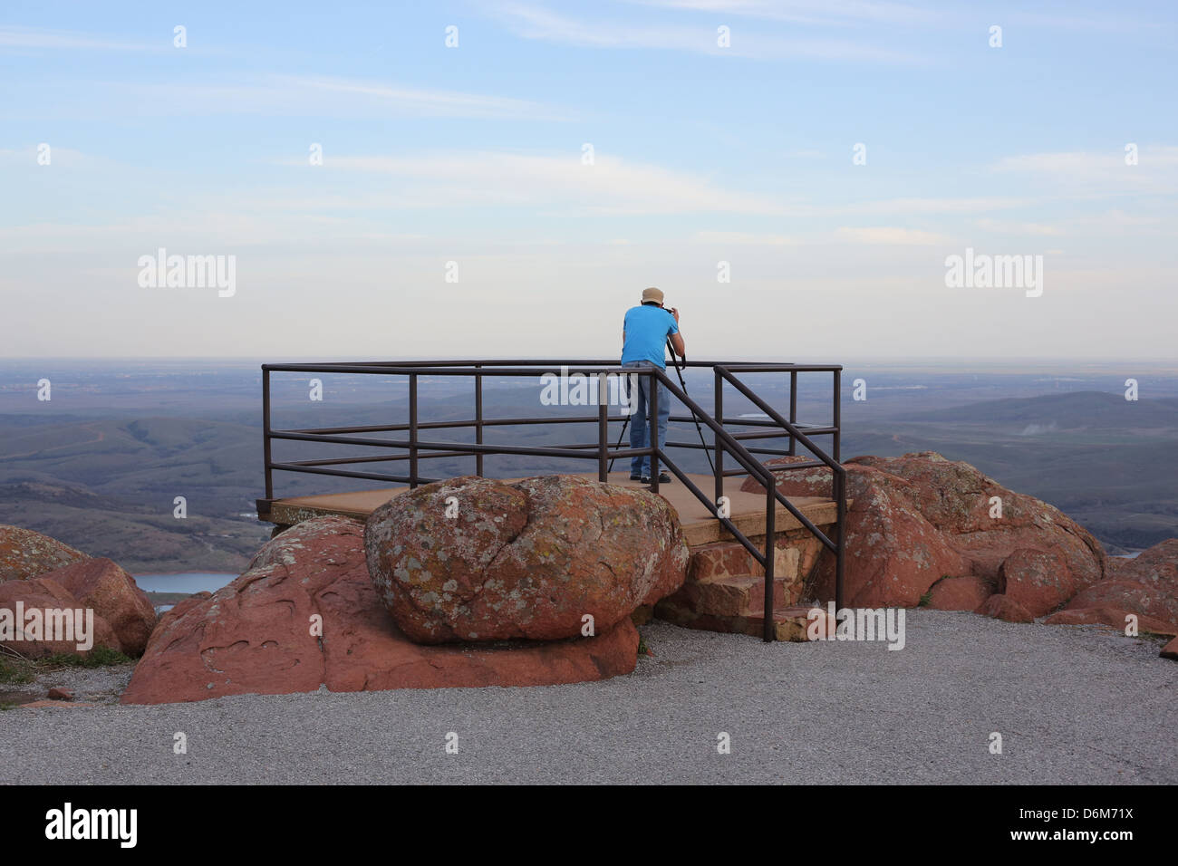 A man taking a photo at the top of Mount Scott in the Wichita Mountains in Oklahoma. - Stock Image
