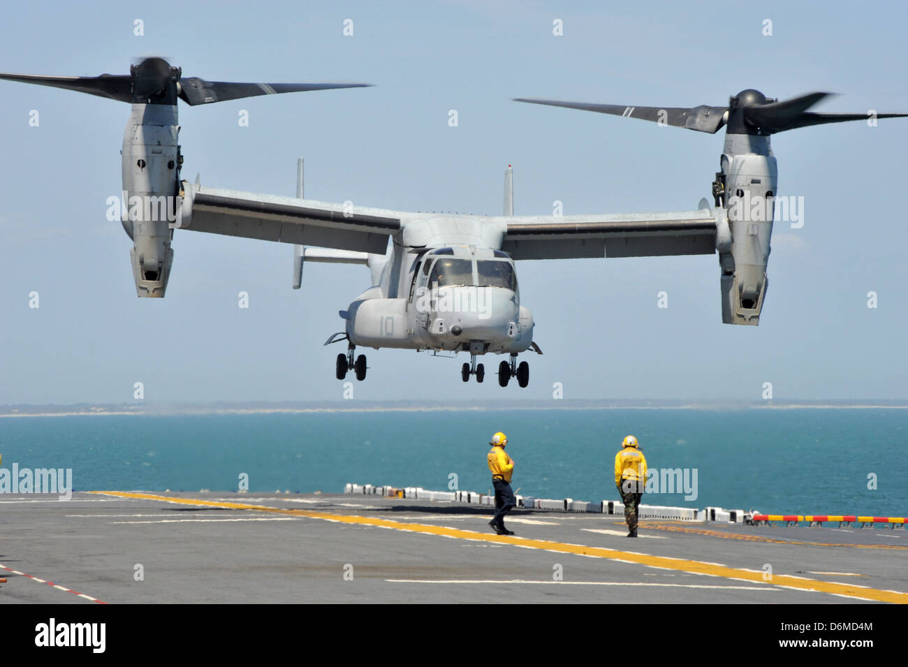 US Navy flight operations sailors direct a MV-22 Osprey aircraft to land on the deck of the multipurpose amphibious - Stock Image
