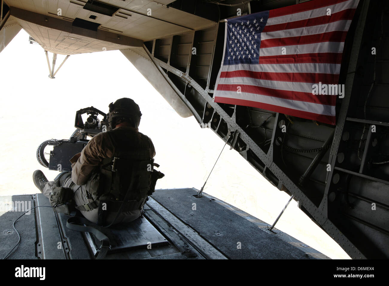 A US Marine door gunner provides security from a CH-53E Super Stallion helicopter during operations April 10, 2013 - Stock Image