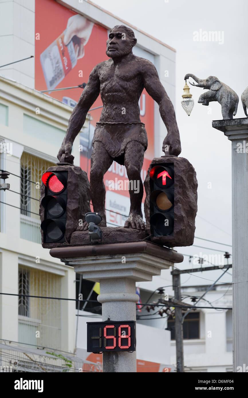 Cavemen or Neanderthal man holding traffic lights in Krabi town, Thailand - Stock Image