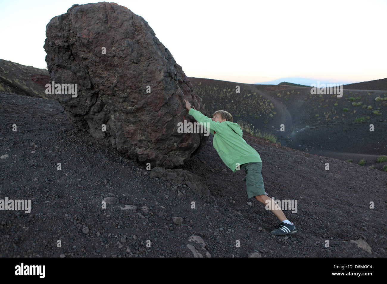 Catania, Italy, Sisyphus, a boy tries a lava rock to roll up a slope - Stock Image
