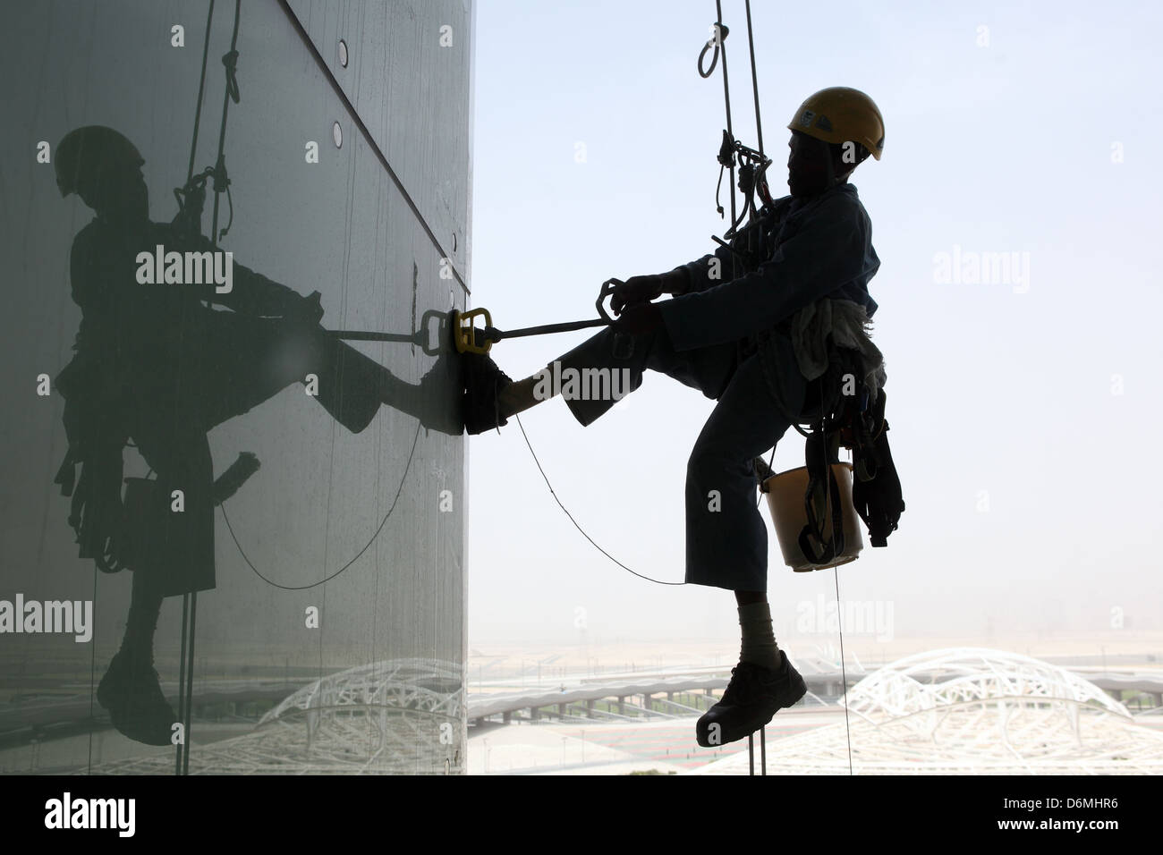 Dubai, United Arab Emirates, silhouette, window cleaners at work on a glass facade Stock Photo