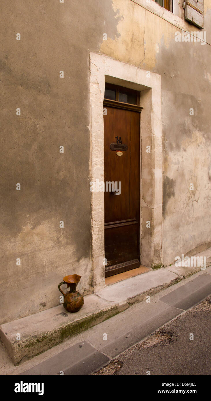 Ancient door in stone frame, ewer on step, Arles, Provence, France Stock Photo