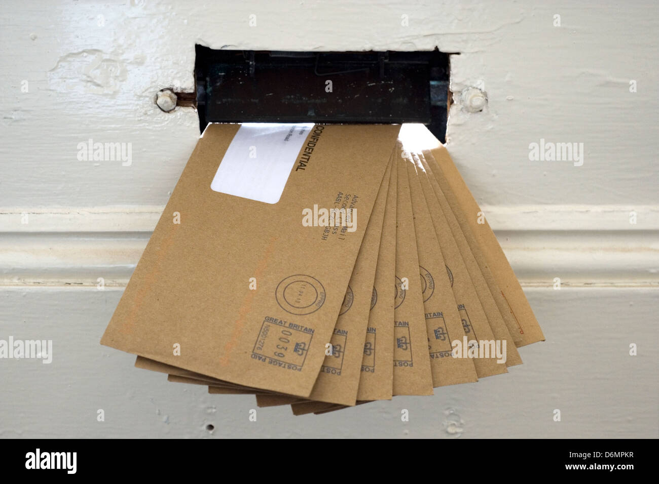 sheaf of brown letters bills hanging in letter box - Stock Image