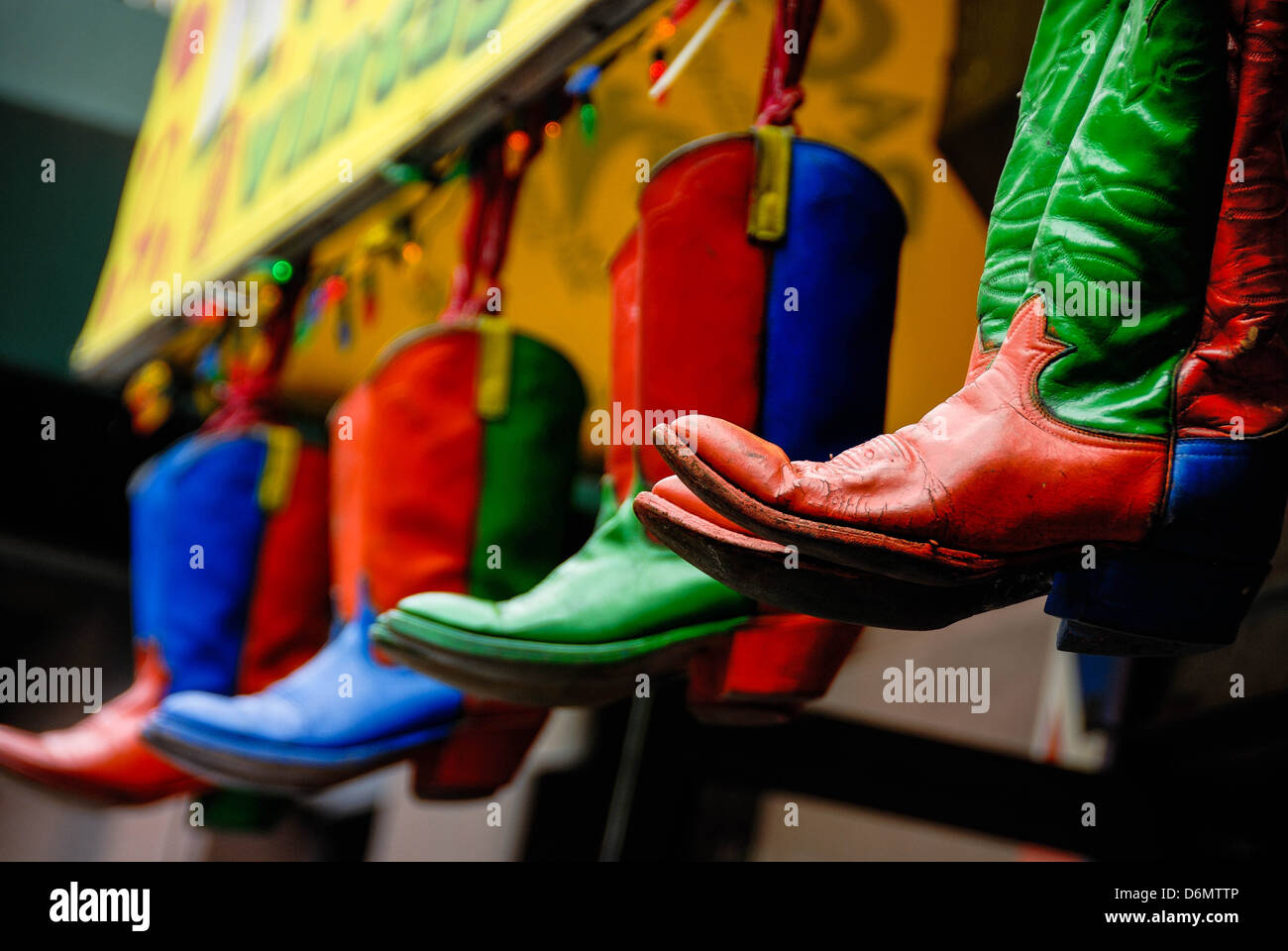 These colorful cowboy boots hang outside a New York city shop. Stock Photo