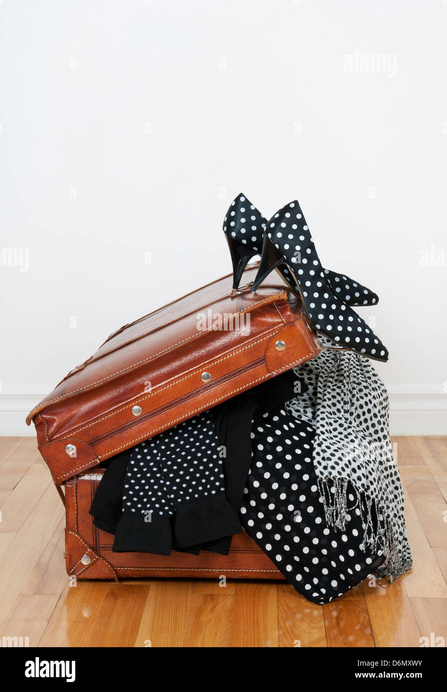 Black and white polka dot clothes and shoes in a vintage leather suitcase. - Stock Image