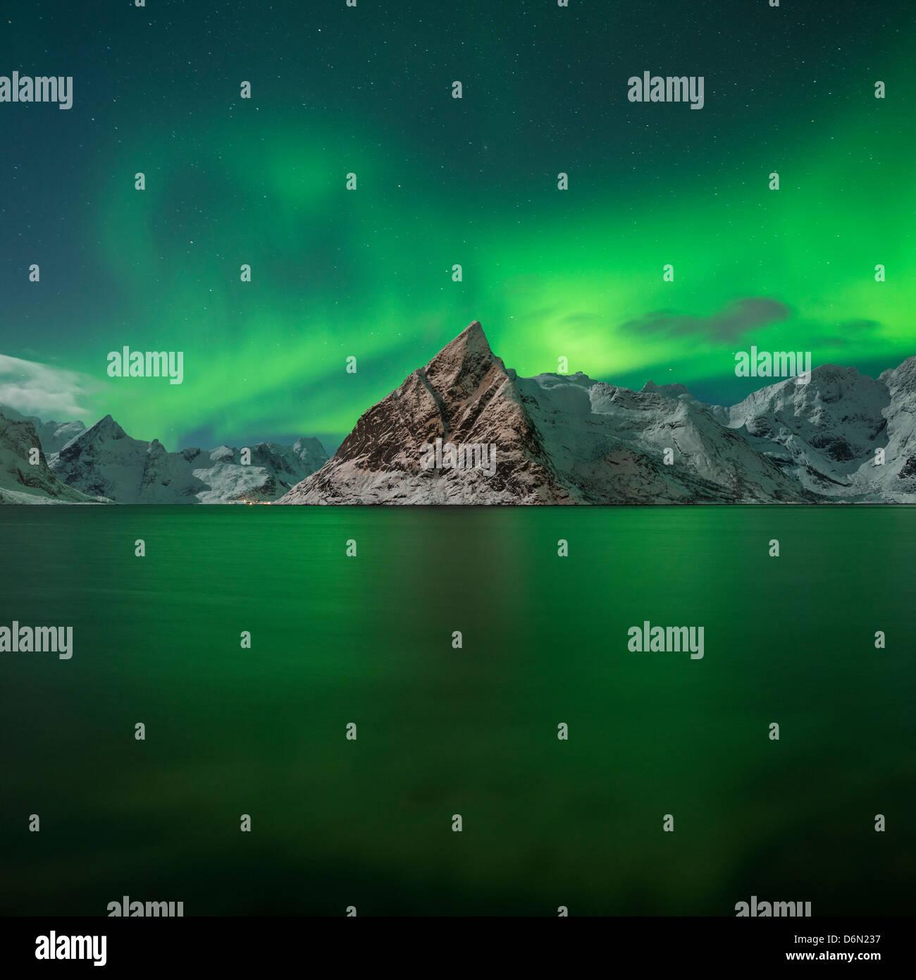 Aurora Borealis - Northern Lights fill sky over Olstind mountain peak and reflect in fjord, Toppøya, Lofoten Islands, Stock Photo
